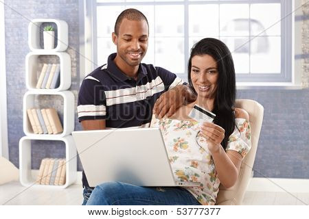 Diverse couple e-shopping at home, using credit card, smiling.