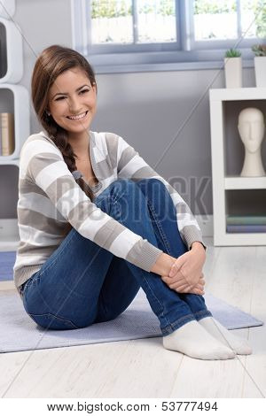 Full size portrait of beautiful young woman sitting on floor at home, arms folded around knee, smiling happily.