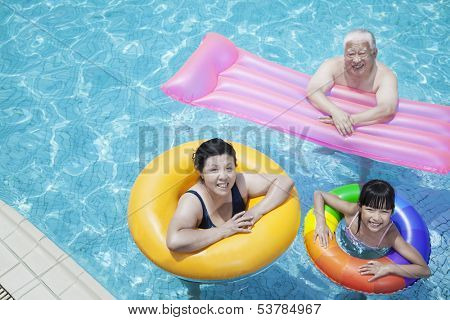 Multi-generational family playing in pool with inflatable tubes