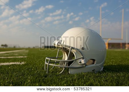 American Football Helmet on the Field with Goal Posts Beyond