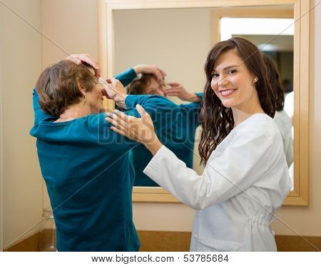 Portrait of female ophthalmologist assisting senior woman to insert contact lens in front of mirror