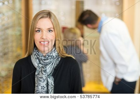 Portrait of mid adult smiling woman with optometrist and son in background at store