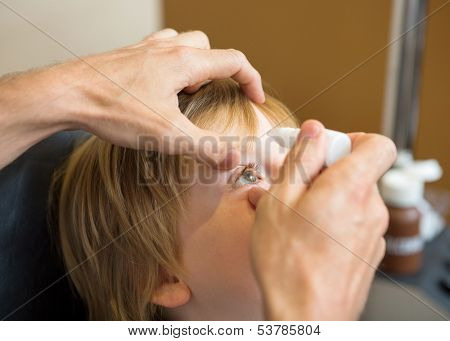 Closeup of optometrist hands putting eye drops in patients eye in clinic