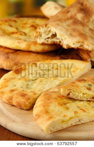 Pita breads on wooden stand close up