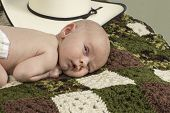 picture of baby cowboy  - An infant baby laying down surrounded by a cowboy hat - JPG