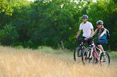 Young Happy Couple Riding Mountain Bikes Outdoor. Healthy Lifestile Concept