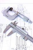 foto of micrometer  - Micrometer and caliper on blueprint vertical - JPG
