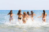 Summer vacation group of six girls playing in the sea