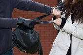 image of stealing  - A thief stealing a black leather backpack - JPG