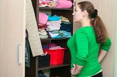 Young Caucasian Woman In The Wardrobe Selecting Things For Wear.