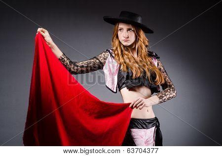 Redhead woman toreador against grey background