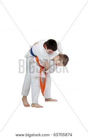 Capture for throw is performing athlete  with orange belt