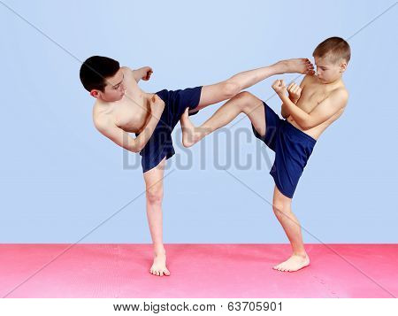 Boys in shorts are beating blows kicks