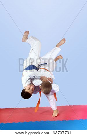 On a light background athletes is doing judo throws