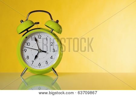Green Alarm Clock, Close Up. A Yellow Background
