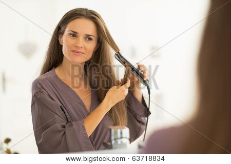 Young Woman Straightening Hair In Bathroom