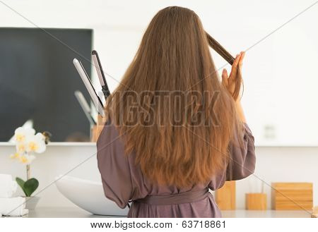 Young Woman Straightening Hair In Bathroom. Rear View