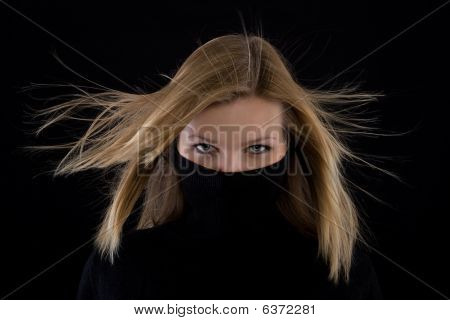 Girl Covers Her Mouth With A Black Turtleneck