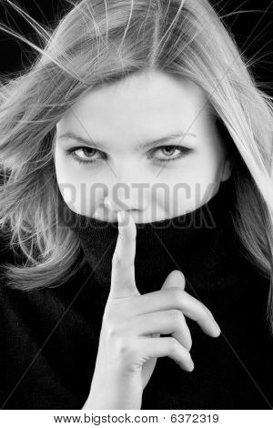 Black And White Photo Of A Girl Making A Hush Gesture