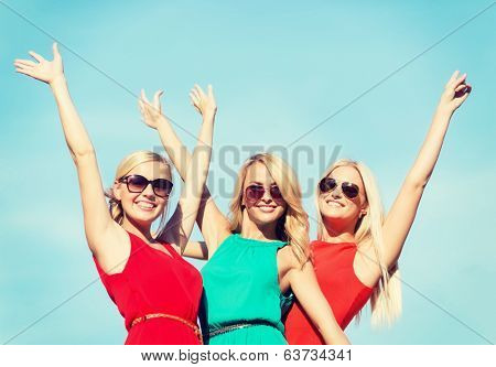 holidays and tourism, friends, hen party, blonde girls concept - three beautiful women waving hands over sky background