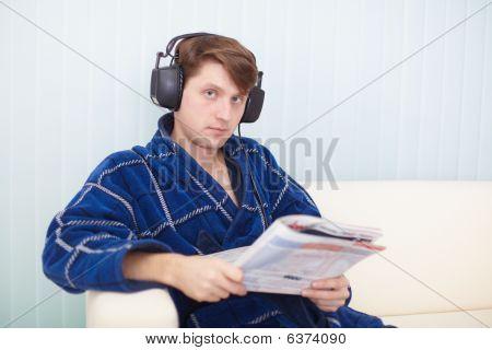 Man In Big Ear-phones On Sofa Reads Newspaper