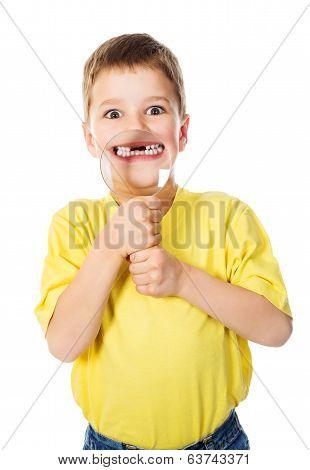 Boy showing teeth through a magnifying glass