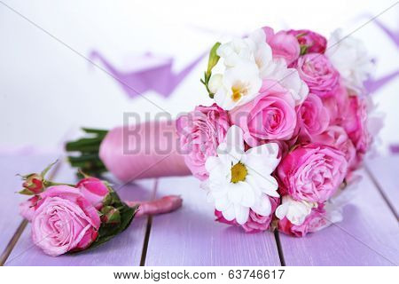 Beautiful wedding bouquet and boutonniere on table on bright background