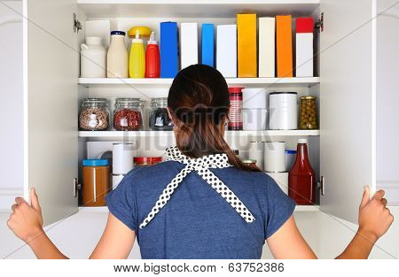 A woman seen from behind opening the doors to a fully stocked pantry. The cupboard is rilled with various food stuff and groceries all with blank labels. Horizontal format the woman is unrecognizable.