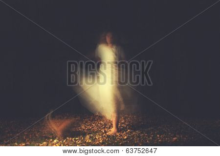 a woman in a very foggy forest at night