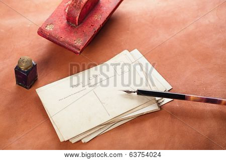 vintage red leather ink blotter  with retro post cards on leather table, shallow dof