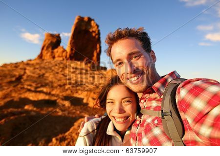 Happy couple taking selfie self-portrait photo hiking. Two friends or lovers on hike smiling at camera outdoors mountains by Roque Nublo, Gran Canaria, Canary Islands, Spain.