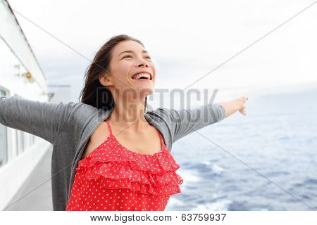 Cruise ship woman on boat in happy free pose smiling enjoying freedom. Young woman traveling on vacation travel sailing on open sea ocean. Young mixed race Asian Caucasian woman.