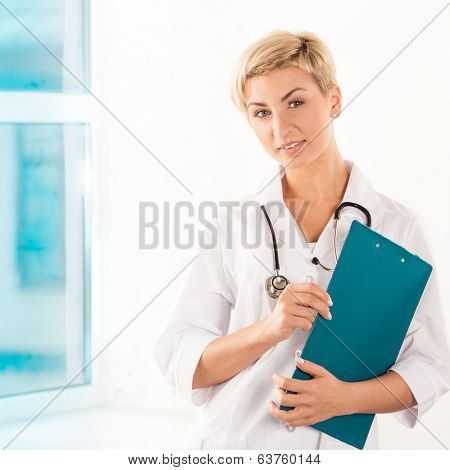 Young doctor in white coat with green tablet in hospital