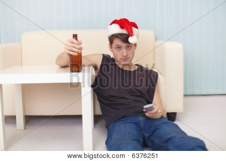 Young Man In Christmas Hat Sits On A Floor With Beer