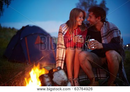 Young couple sitting by the fire and drinking tea outside
