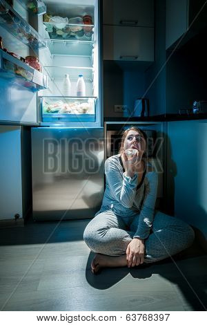 Woman In Pajamas Eating On Floor Next To Fridge At Night