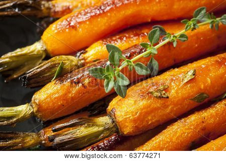 Roasted baby carrots garnished with thyme.