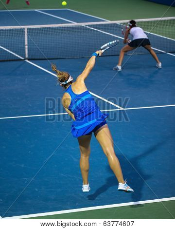 KUALA LUMPUR - APRIL 20, 2014: Timea Babos of Hungary (blue) serves during the doubles final of the BMW Malaysian Open Tennis in Kuala Lumpur, Malaysia. She partners Chan Hao-Ching to emerge winners.
