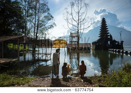BALI - APRIL 11, 2014: Balinese Hindu devotees go to pray at an ancient temple on Lake Batur, a volcano crater lake in Bali, Indonesia. Religious rituals and ceremonies are a way of life in Bali.