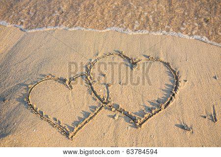 heart on wet golden beach sand