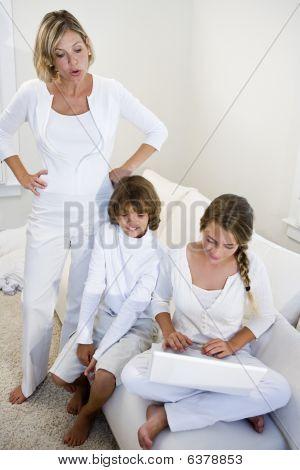 Mother watching children using laptop