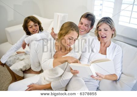 Family sitting on sofa together looking at book mom is reading