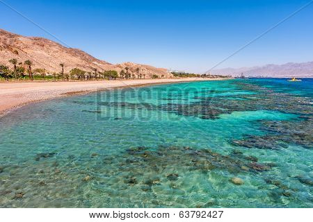 Aquamarine water and underwater corals along empty beach on popular resort of Eilat on Red Sea in Israel.