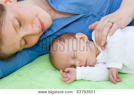 Smiling Mother Sleeping With Her Newborn Baby