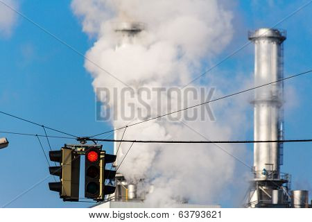 chimney of an industrial company and a red light. symbolic photo for environmental protection and ozone.