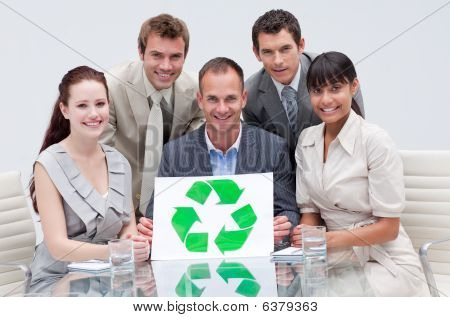 Smiling Business Team Holding A Recycling Symbol. Ecological Business