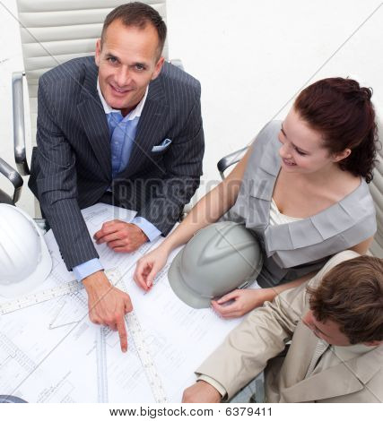 Architect Man Pointing At A Plan In A Meeting