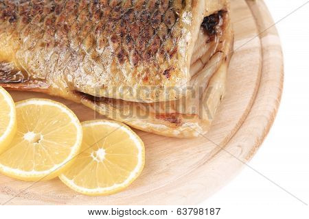 Fried carp on wooden platter with lemon.