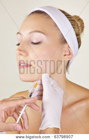 Woman in beauty clinic getting cosmetic surgery with syringe