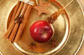 stock photo of ouzo  - Red apple cinnamon and anise stars on golden plate - JPG